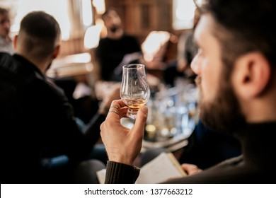 A close up shot of a young european man tasting Japanese whisky. Concept of fine alcohol. Master class and degustation of whisky.