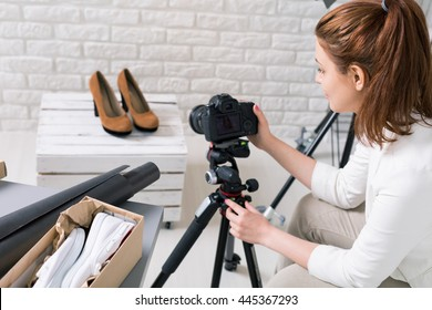 Close shot of a young fasioner making photo of high-heeled shoes using the tripod in her atelier