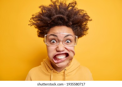 Close up shot of young irritated Afro American woman stares bugged eyes through transparent glasses keeps mouth opened dressed in sweatshirt isolated over yellow background. Mad crazy female
