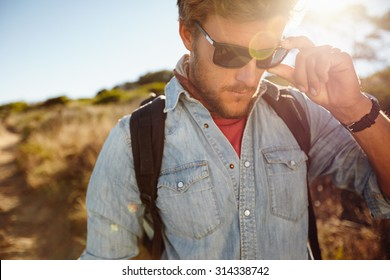 Close up shot of young man on country hike. Caucasian male model hiking wearing sunglasses with sun flare.