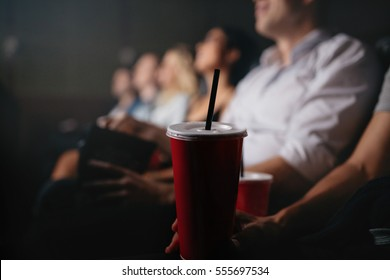 Close up shot of young people with soft drinks in movie theater, focus on cold drink glass.