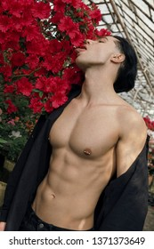 Close up shot of young shirtless handsome man with nipple piercing posing against wall of red flowers
