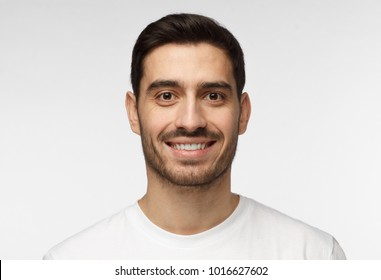 Close up shot of young smiling man isolated on grey background