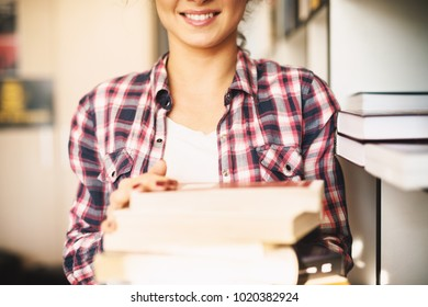 Close shot of young smiling student girl standing in the library and holding book stack.