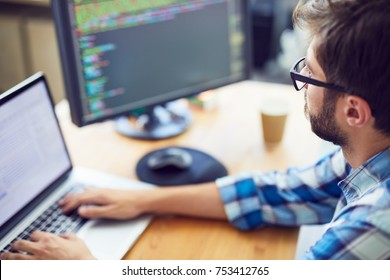 Close up shot of a young software developer, programmer  working at his desk