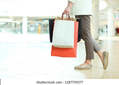 Close up shot of young woman leg carrying colorful shopping bags while walking in shopping mall.