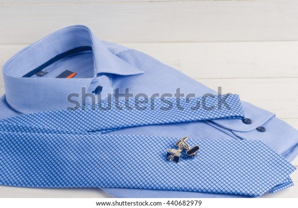 Close up shots of blue striped man's shirt with blue dotted tie and cuff links. striped folded shirt with a tie isolated on white background.