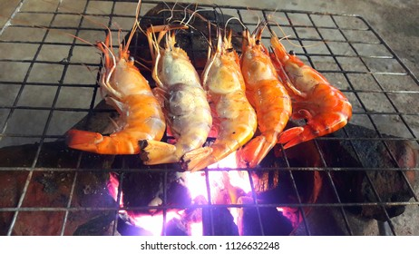 Close up of shrimp grilled on a hot charcoal stove in party at house.