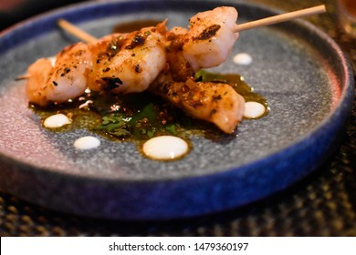 close up of shrimp on squires with white dots of sauce with herbs and spices on a round plate upscale evening appetizer