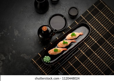 close up of shrimp  sushi set with chopsticks and soy on stone table. Top view