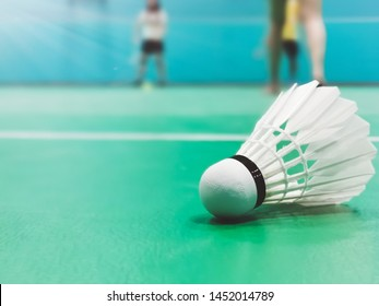 Close up shuttercock detail on badminton green court with blurred badminton players in background. Indoor sport concept.