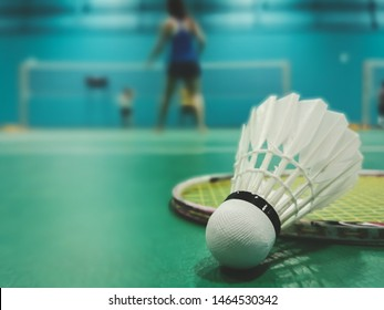 Close up shuttercock detail on badminton racket and green court with blurred badminton players in background. Indoor sport concept.