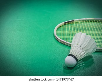Close up shuttercock detail on badminton racket and green court background. Indoor sport concept.