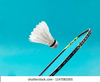 Close up shuttlecock and badminton racket on blue background.