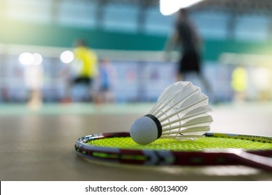 Close up shuttlecock on racket badminton at badminton courts with players competing
