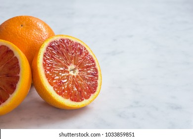 Close Up of Sicilian Blood Oranges, Sliced in Half and Whole, on Gray Marble Counter