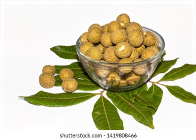 Close up and side angle view of Fresh longan or Dimocarpus longan fruits in a glass bowl on white isolated background with green leaves.