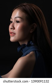 Close up side portrait of beautiful asian woman with long hair smiling on dark background.  Asian young model in studio.