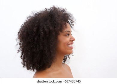 Close up side portrait of beautiful black woman smiling against white background