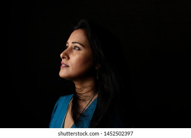 Close up side portrait of a beautiful Indian Bengali brunette woman in light and shadow before a black copy space background wearing a blue top. Indian lifestyle and fashion  portrait