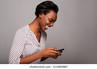 Close up side portrait of beautiful woman holding mobile phone and laughing