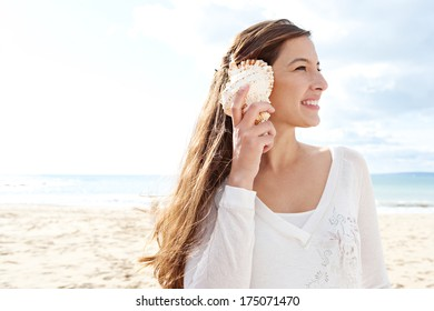 Close up side portrait of a beautiful young woman on holiday on a beach holding a sea shell to her ear and smiling, listening to the sound of the ocean against blue sky. Outdoors lifestyle.