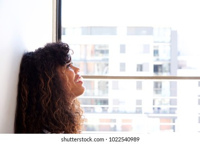 Close up side portrait of happy young woman leaning against wall and looking up