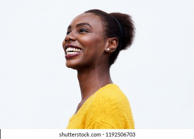 Close up side portrait of happy young african american woman laughing against isolated white background