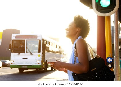 Close up side portrait of smiling african american woman with cell phone on the city street