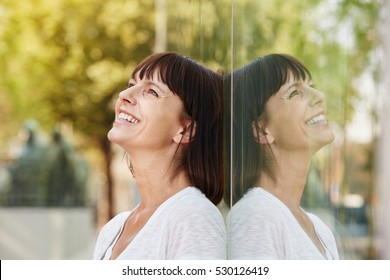 Close up side portrait of smiling friendly woman leaning against reflection in building