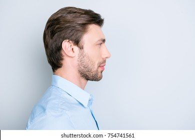 Close up side portrait of young bearded manager standing over grey background with copy space