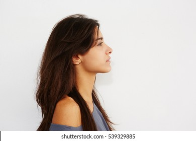 Close up side portrait of young female standing against while wall