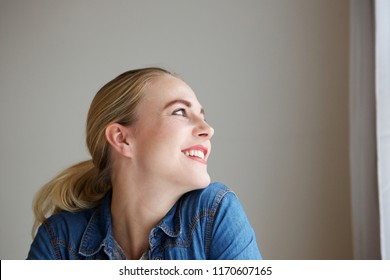Close up side portrait of young woman smiling and looking away