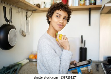 Close up side portrait of young woman in kitchen with digital tablet thinking of what to cook