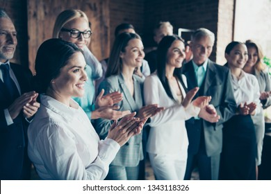Close up side profile blurry view photo different age members business people stand she her he him his together best brigade show appreciation clap hands arms project power formal wear jackets shirts