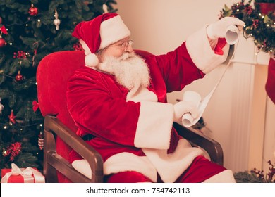 Close up side profile of concentrated santa study list of children's wishes and gifts on whatman, ready to make dreams come true, bring happiness to kids. Holly jolly x mas, noel time