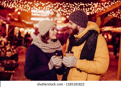Close up side profile photo of beautiful young couple outdoors at winter on a new year`s eve with hot drinks, looking at each other, so tender, romantic, tempting, sensual. True love and feelings