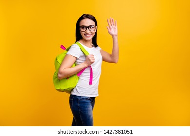 Close up side profile photo beautiful she her lady backpack meet classmates groupmates classes lessons wave arm say hi wear specs casual white t-shirt jeans denim isolated bright yellow background