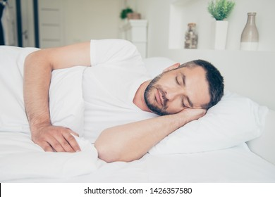 Close up side profile photo fall asleep he him his attractive guy vacation sunday saturday daily dream eyes closed lean head arm hand white nightwear sleep wear t-shirt lying bed bright room indoors