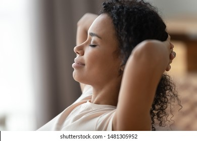 Close up side profile view of calm happy african American young woman relax hands over head dreaming or visualizing, peaceful black millennial girl sleep rest at home, daydreaming, stress free concept