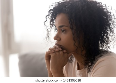 Close up side profile view of pensive young african American woman thinking of relationships problems, thoughtful black biracial female feel despair lost in thoughts consider life trouble or drama