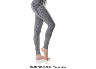 Close up side sexy view of woman legs stretching the muscles of the foot in gray sports thermal underwear with pattern on white background.