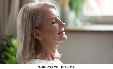 Close up side view 50s blonde woman closed eyes feels calm and serene enjoy free time at home, life without stress, good healthy habit at retired life practises of breathing techniques do yoga concept
