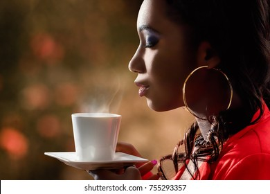 Close up side view of attractive african woman smelling scent of hot beverage.Low key portrait of woman with directional back lit ambient light holding cup with coffee.