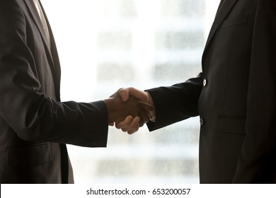 Close up side view of black and white hands shaking, businessmen in formalwear handshaking, caucasian and afro american partners closing deal, forming international partnership, multi ethnic team