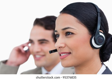 Close up side view of call center agents against a white background