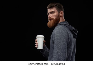 Close up side view dramatic shot of handsome young bearded man having coffee outside Male taking rest and drinking fresh morning coffee to go Side view shot of young athlete with coffee in hand.