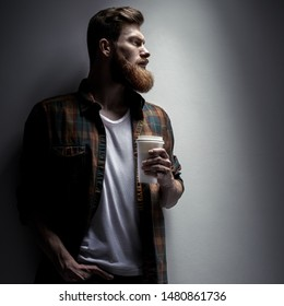 Close up side view dramatic shot of handsome young bearded man having coffee indoors Male taking rest and drinking fresh morning coffee to go Side view shot of young businessman with coffee in hand