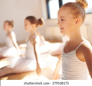 Close up side view of the face of a cute pretty little blond ballerina smiling in class as she practices her poses with her classmates in a warm bright ballet studio