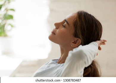 Close up side view female face with closed eyes putting hands behind head resting after busy fruitful working day. Student take a break relaxing feeling good having inner balance. No stress concept